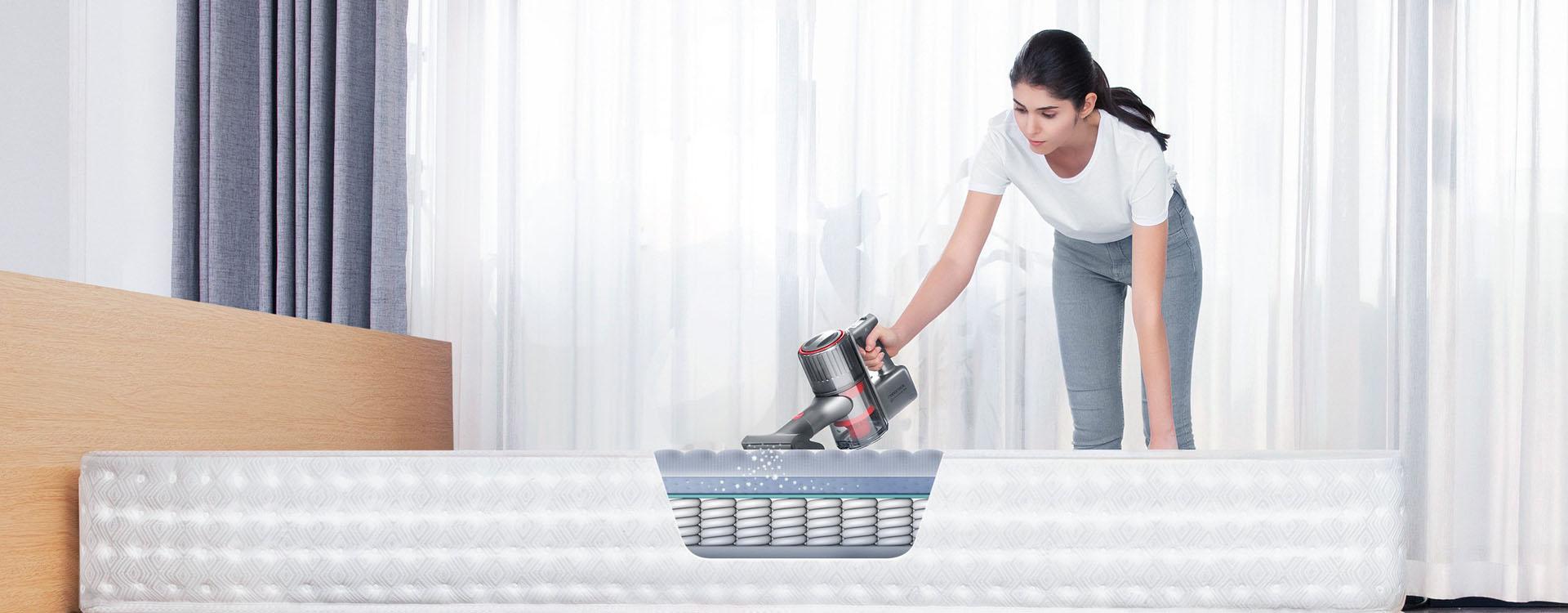 Kobieta czyści materac odkurzaczem Roborock H6.